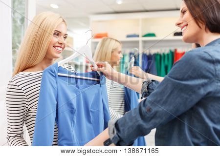 Try on this dress. Pretty young woman is holding clothing near her friend. They are standing and smiling in shop
