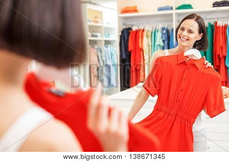 Beautiful young girl is trying on red dress in shop. She is standing and looking at mirror with pleasure. Woman is smiling happily