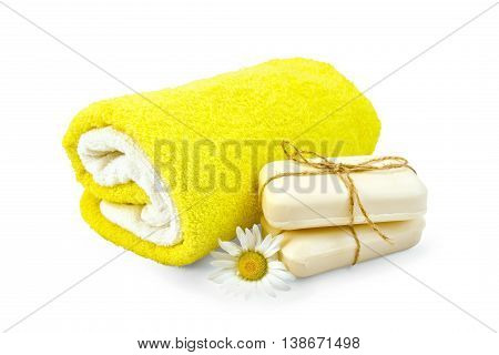 Two bar of soap, tied with twine, chamomile flower and towels isolated on white background