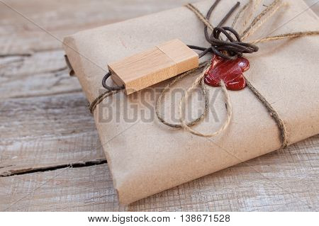 The parcel wrapped in Kraft on a wooden background. The gift wrapped in Kraft. Wooden USB stick. Cord and red sealing wax.
