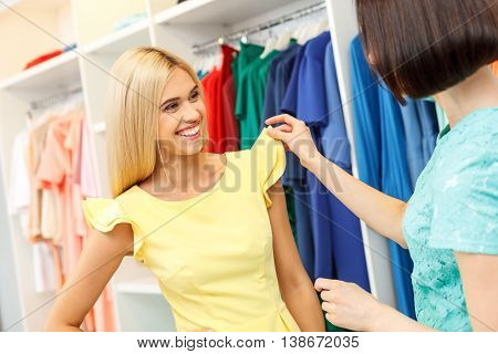 This dress is very beautiful. Young woman is wearing new clothing in shop. She is posing and smiling. Her friend is touching cloth with interest