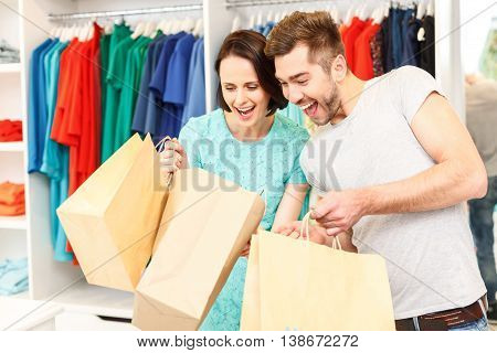 Happy loving couple is going shopping together. They are holding packets and looking inside with happiness. Man and woman are standing in shop and smiling
