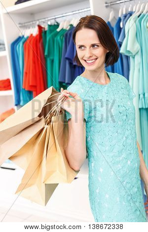 Stylish young woman is purchasing in boutique. She is standing and carrying many packets. Lady is standing and smiling