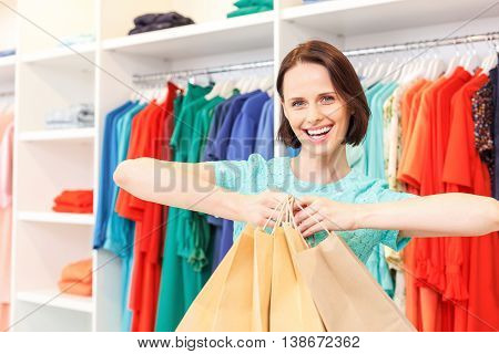 Joyful young girl is shopping in boutique. She is standing and showing many packets of bought clothing. Woman is looking at camera with happiness and smiling