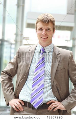 Closeup of a young smiling business man standing in a light and mordern business hall