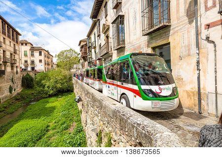 Granada, Andalucia, Spain - April 16, 2016: Granada City Tour with the shuttle along the Carrera del Darro in the popular old Moorish Albaicin quarter. It's located on a hill facing the Alhambra.