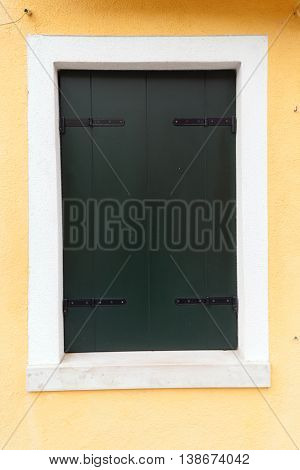 Picturesque old window with dark green shutters on light yellow wall (Burano island Venice Italy)
