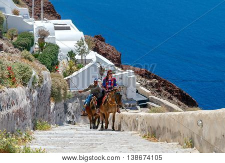 Santorini, Greece - April 28, 2016: Ride horseback on donkeys from the harbor to the village at the top of the cliffs. A popular tourist attraction on the island of Santorini.