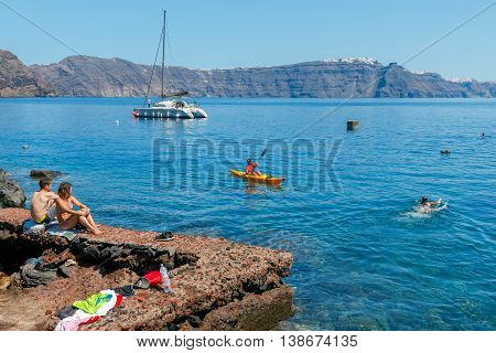Santorini, Greece - April 28, 2016: The rocky beach near the village of Oia on Santorini. The harbor is visited by large number of tourists.