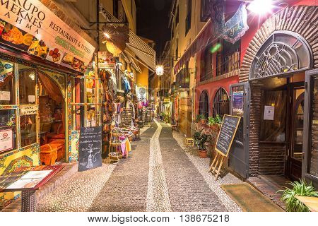 Granada, Andalucia, Spain - April 16, 2016: typical restaurants and shops in a street of the popular old Moorish quarter Albaicin illuminated at night. The historical center of Granada Town.