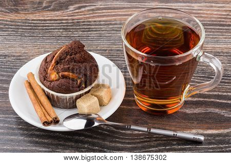 Cupcake in saucer cinnamon sticks sugar and tea on wooden table