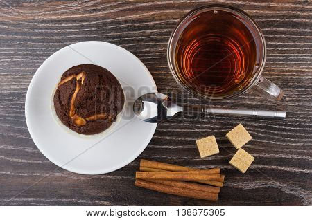 Cupcake in saucer cinnamon sticks sugar and tea on wooden table. Top view