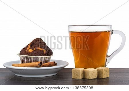 Cupcake in saucer cinnamon sticks sugar and tea isolated on white background. Side view