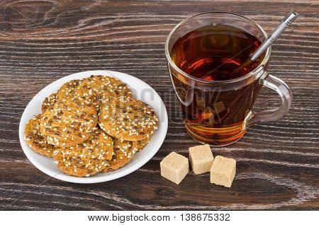 Cookies with sesame seeds in saucer tea and sugar on wooden table