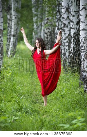 Beautiful young caucasian brunette woman in red dress outdoors whole-length portrait flexibility and stretching on nature