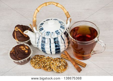 Tea teapot cookies cupcakes and cinnamon sticks on wooden table