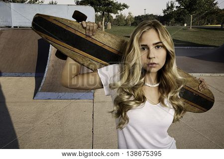 Beautiful blond girl wearing white shirt and jean shorts standing with skateboard in a skate park.