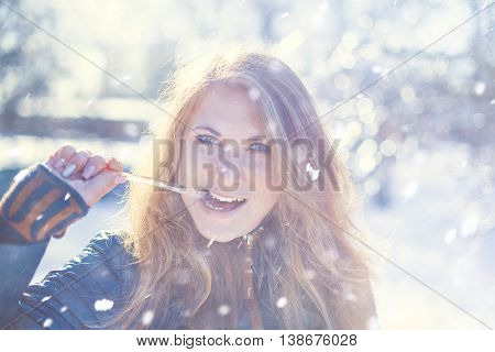 Photo of a beautiful girl with an icicle in mouth