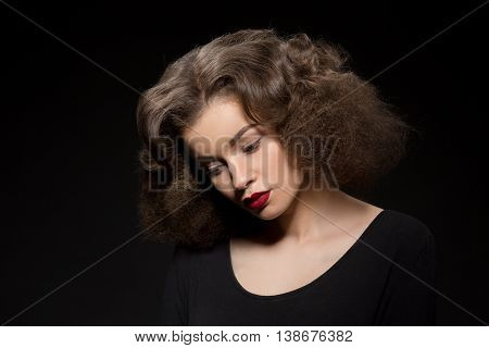 Closeup portrait of beautiful lady with red lips looking downwards. Pretty lady with modern hairstyle isolated over black background.