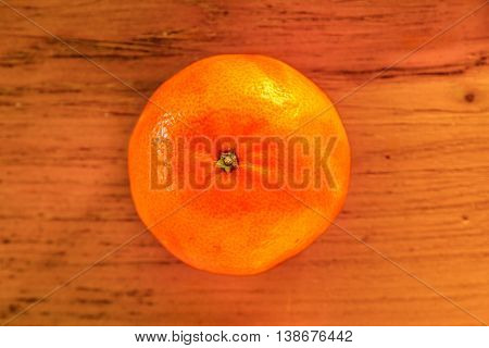 Whole not peeled tangerine on wooden board