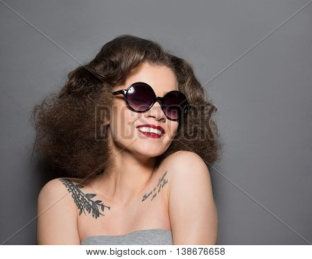 Portrait of happy beautiful lady in sunglasses posing over grey background. Smiling lady demonstrating her modern hairstyle in studio.