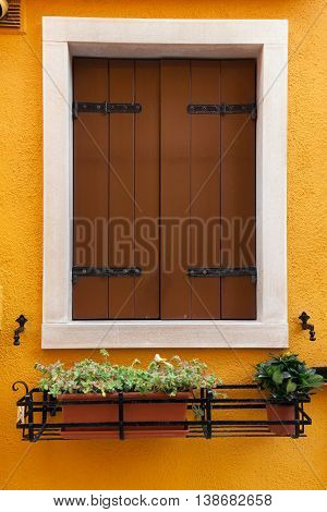 Picturesque old window with brown shutters on dark yellow wall (Burano island Venice Italy)