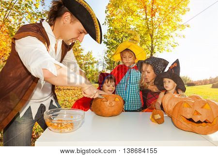 Father in pirate costume crafts Jack-O'-Lantern with is family from pumpkin sitting at the table outside during beautiful sunny autumn day