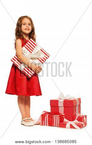 Beautiful little 6 years old girl stand close to pile of many presents isolated on white