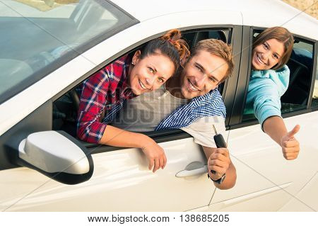 Cheerful guy with two girls in the car ready for a trip - Group of friends are excited for the next holiday destination - Concept of freedom inclusion transport and travel main focus on guy face