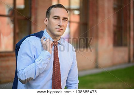 Successful middle aged businessman is resting outdoors after work. He is standing near building and holding jacket behind back. Man is looking at camera with confidence
