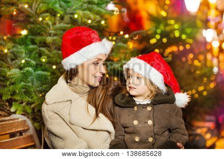Mather and daughter talking about holidays sitting on the bench near the spruce decorated with garland