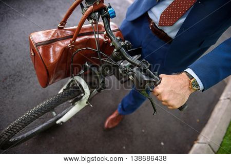 Top view close-up of man riding bicycle to work. He is standing on road while carrying suitcase on steering wheel