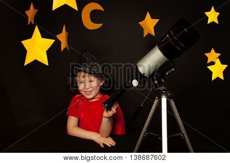 Happy five years old boy in sparkling cap and red cape with a telescope on black background