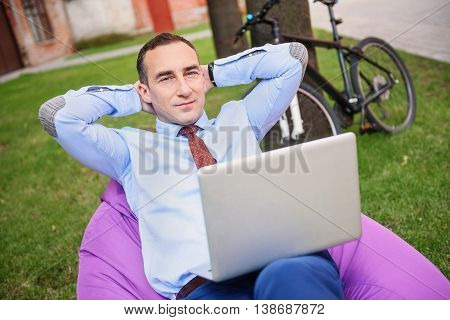Cheerful businessman is working on laptop in his garden. He is sitting on chair and relaxing. Man is looking at camera with confidence. His bicycle and house on background