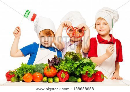 Three young cooks, girl and boys in uniform, holding Italian flags and paper rings, isolated on white