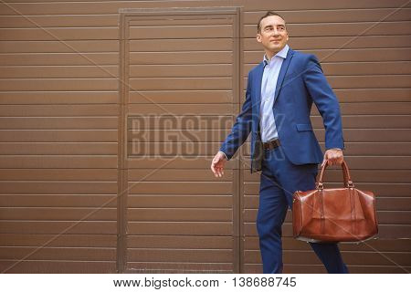 Finally vacation. Joyful businessman is walking with suitcase near building. He is smiling. Copy space in left side