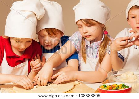 Four young chefs in cook's uniform having fun making homemade cookie with cookie cutters, close-up