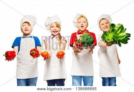 Four kids in cook's uniform standing in a row, holding fresh vegetables, isolated on white