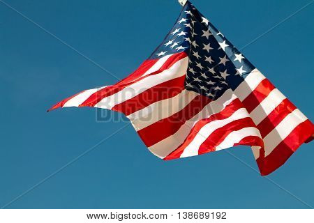 United States flag blows in the wind against a blue sky attached to the wall from the side