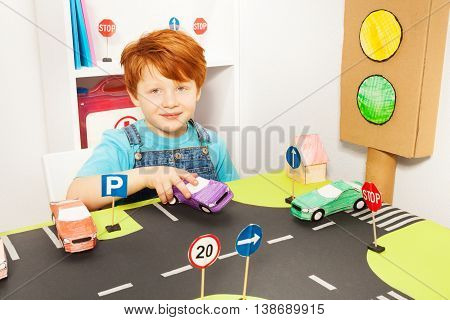 Portrait of five years old redheaded boy, playing driver with toy handmade paper car and light-signal at the road playing field