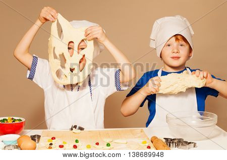 Two young bakers, boys in aprons and toques, having fun kneading dough for cookies