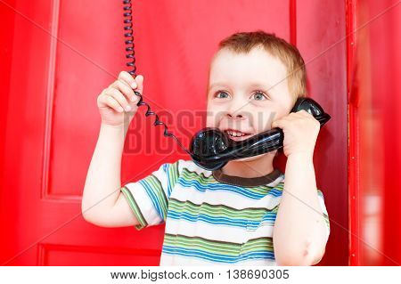 child holding a telephone receiver and smiling. cute boy talking on the phone in a red telephone box. the concept to share with the family joy and impressions