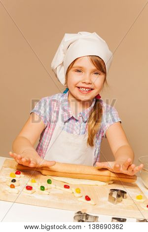 Little smiling girl playing baker, and making dough using rolling pin on the wooden desk