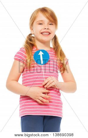 Close-up picture of smiling seven years old girl with pigtails, holding miniature of blue road direction sign, isolated on white