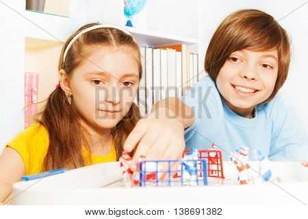 Two kids, boy and girl playing ice hockey table board game in the playroom