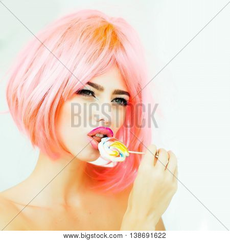 young sexy woman with bright makeup on pretty face and orange hair lick lollipop candy on white background