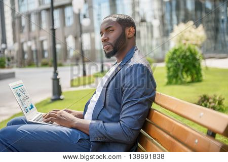 Young African businessman is waiting for someone in city. He is sitting on bench and looking aside pensively. Man is holding laptop