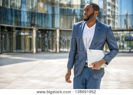 Confident African businessman is standing near office and carrying laptop. He is looking forward with anticipation