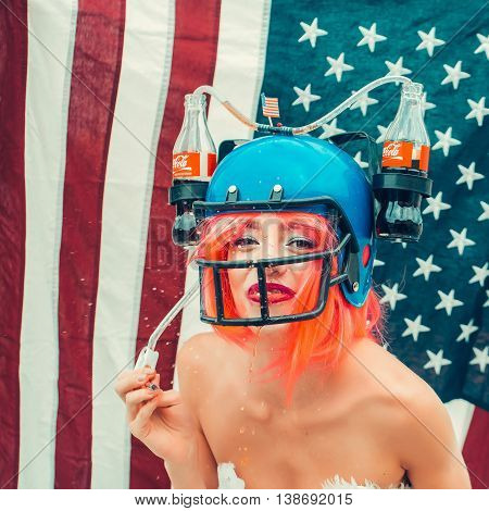 Ukraine Kyiv - July 27 2016: young patriotic sexy woman with pretty smiling face and orange hair in american football drink helmet with coca cola on flag background celebrating independence day usa