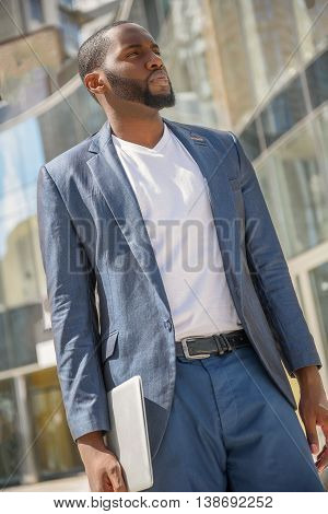 Serious young man is standing outdoors with computer. He is looking forward with expectation